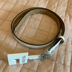 Michael Kors thin white belt with silver MK logo.